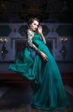 Härlig kvinna i en grön lång klänning på en bakgrund av rikt fotografering för bildbyråer