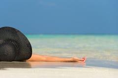 Härlig kvinna i en hatt som ligger på en tropisk strand Arkivfoto