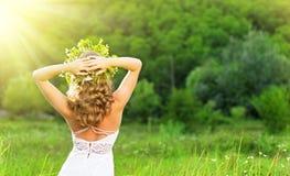 Härlig kvinna i en krans av blommor på naturen Arkivfoto
