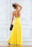 Härlig kvinna i en lång gul klänning. arkivfoton