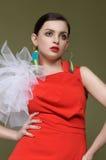 Härlig kvinna i en röd klänning och örhängen från etiketter från clo Arkivbilder