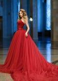 Härlig kvinna i en röd lång klänning och en guld- krona i gren Royaltyfria Bilder