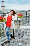 Härlig kvinna i en röd tröja som poserar nära stängerna Fotografering för Bildbyråer