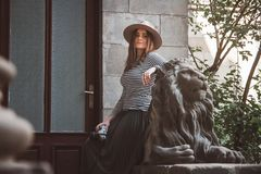 Härlig kvinna i en randig skjorta och en hatt Rymmer kameran nära statyn av ett lejon mot bakgrunden av det gammalt arkivfoton