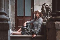 Härlig kvinna i en randig skjorta och en hatt Rymmer kameran nära statyn av ett lejon mot bakgrunden av det gammalt royaltyfri fotografi