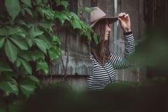 Härlig kvinna i en randig skjorta som rymmer hennes hatt royaltyfri bild