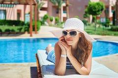 Härlig kvinna i en stor vit hatt på en dagdrivare vid pölen Royaltyfri Fotografi