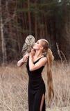 Härlig kvinna i en svart klänning med en uggla på hans arm Blondin med långt hår i naturen som rymmer en uggla Romantisk delikat  Royaltyfria Foton