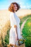 Härlig kvinna i en vit klänning med en korg med bröd och mi Arkivfoton