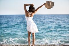 Härlig kvinna i en vit klänning som går på stranden Avkopplad kvinna som andas ny luft, emotionell sinnlig kvinna nära havet Arkivbilder