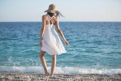 Härlig kvinna i en vit klänning som går på stranden Avkopplad kvinna som andas ny luft, emotionell sinnlig kvinna nära havet, enj Royaltyfri Fotografi
