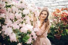Härlig kvinna i enfärgad klänning med ett långt drev fotografering för bildbyråer