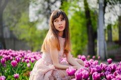 Härlig kvinna i ett fält av tulpan Arkivfoton