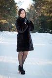 Härlig kvinna i ett pälslag i vinterskogen Arkivfoto