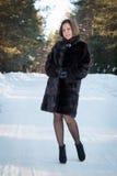 Härlig kvinna i ett pälslag i vinterskogen Royaltyfri Bild