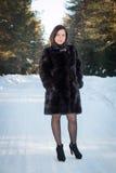 Härlig kvinna i ett pälslag i vinterskogen Fotografering för Bildbyråer