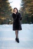 Härlig kvinna i ett pälslag i vinterskogen Arkivbild