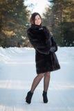 Härlig kvinna i ett pälslag i vinterskogen Royaltyfria Bilder