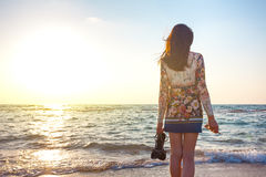 Härlig kvinna, i färgrikt klänninganseende på stranden nära havet och att se långt borta på solnedgången arkivbilder