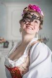 Härlig kvinna i gammalmodig medeltida klänning med maskeringen royaltyfria foton