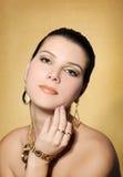 Härlig kvinna i guld- smycken royaltyfri bild