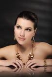 Härlig kvinna i guld- smycken royaltyfria foton
