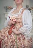 Härlig kvinna i hållande rosa färgros för medeltida klänning royaltyfria bilder