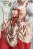 Härlig kvinna i hållande rosa färgros för medeltida klänning arkivfoton
