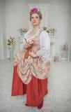 Härlig kvinna i hållande rosa färgros för medeltida klänning fotografering för bildbyråer