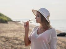 Härlig kvinna i hatt med exponeringsglas av vin på stranden vid havet Arkivfoto