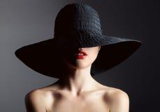 Härlig kvinna i hatt retro mode Stranda av hår vänder mot in Arkivbild