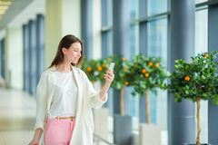 Härlig kvinna i internationell flygplats Turist med den inomhus smartphonen arkivfoto