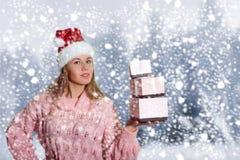 Härlig kvinna i jultomtenhatt med giftboxes på fotografering för bildbyråer