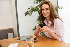 Härlig kvinna i kafé som dricker kaffe royaltyfri bild