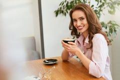 Härlig kvinna i kafé som dricker kaffe royaltyfri fotografi