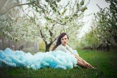 Härlig kvinna i klänning i trädgårdarna Arkivfoto