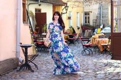 Härlig kvinna i klänning som går i gammal stad av Tallinn, Estland Royaltyfri Foto