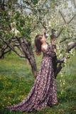 Härlig kvinna i klänning som kramar trädet i trädgård arkivfoto