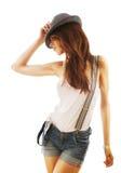 Härlig kvinna i kortslutningar och hatt med hängslen Fotografering för Bildbyråer