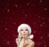 Härlig kvinna i kyss för jullockblows royaltyfri foto
