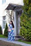 Härlig kvinna i lång klänning som går i gammal stad Arkivfoton