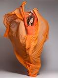 Härlig kvinna i långt orange posera för klänning som är dramatiskt royaltyfri foto