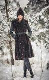 Härlig kvinna i långt svart pälslag och lock som tycker om vinterlandskapet i skogbrunettflickan som poserar under snö-täckt träd Royaltyfria Bilder