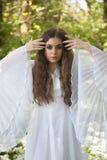 Härlig kvinna i långt vitt klänninganseende i en skog royaltyfria foton