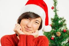 Härlig kvinna i leenden för en santa hatt fotografering för bildbyråer