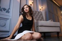 Härlig kvinna i lyxigt inre sammanträde på golvet bredvid fåtöljen Royaltyfri Bild