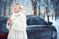 Härlig kvinna i lyxigt vitt pälslag som dricker varmt kaffe på snöig dag och att skratta för vinter Arkivbild