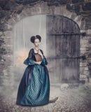 Härlig kvinna i medeltida klänning med boken arkivfoton