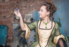 Härlig kvinna i medeltida klänning med den lilla flaskan arkivfoto
