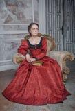 Härlig kvinna i medeltida klänning på fåtöljen arkivfoto